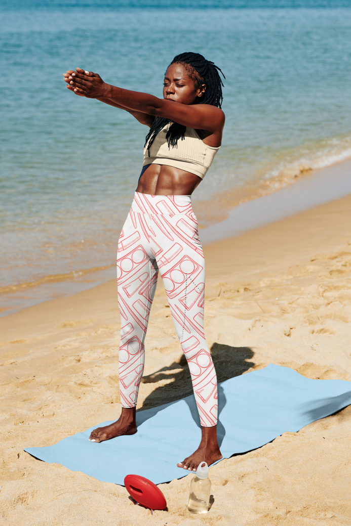 Mockup of a woman wearing sublimated leggings while practicing yoga at the beach 38326 r el2